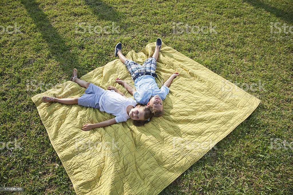 Children having fun lying on picnic blanket stock photo