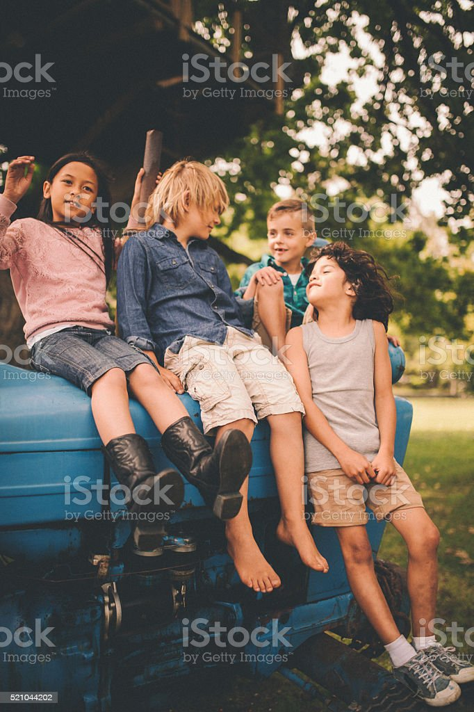 Children having fun on an old tractor together on farm stock photo