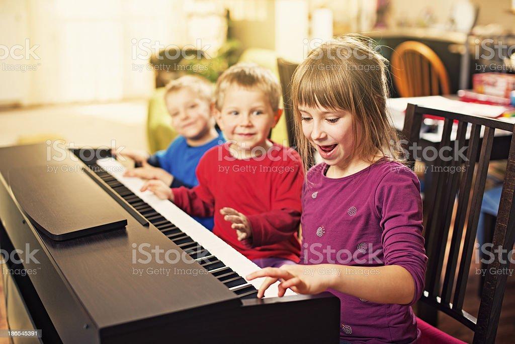 Children having fun playing the piano royalty-free stock photo