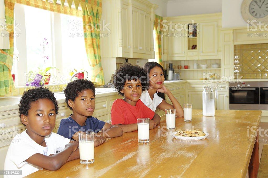 children having milk and cookies stock photo