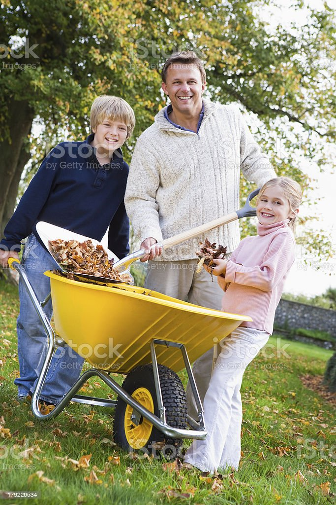 Children helping father to collect autumn leaves stock photo