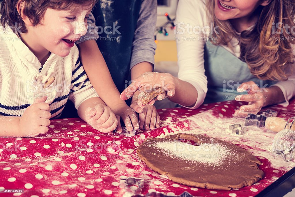 Children helping mother baking cookies for Christmas Eve stock photo
