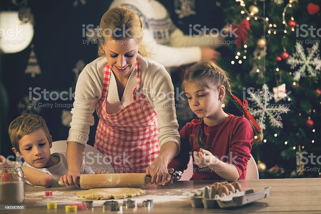 Children helping mother baking cookies for Christmas stock photo