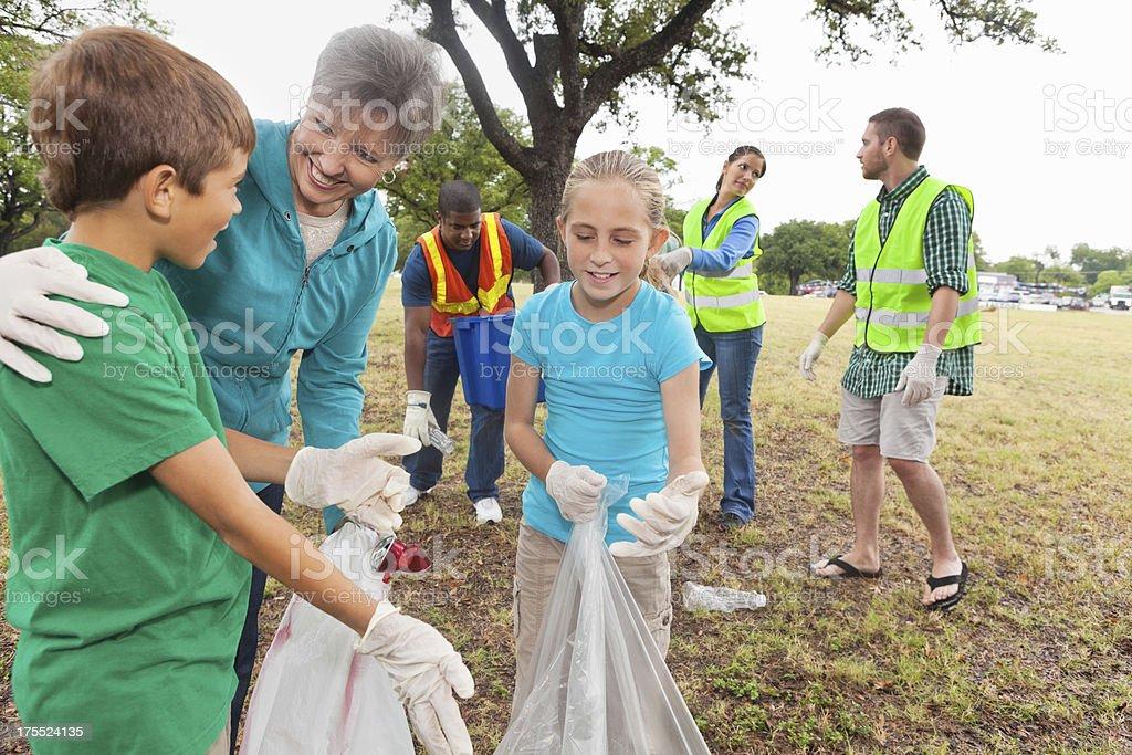 Children helping with volunteer group cleaning neighborhood park stock photo