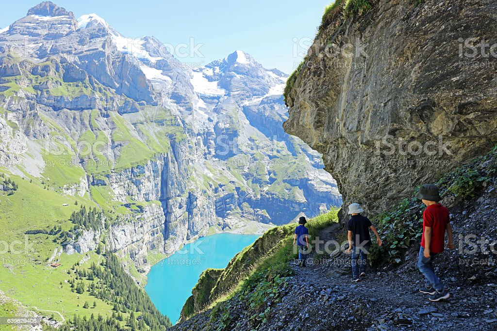 Children Hiking at Oeschinensee in the Mountains in Switzerland stock photo