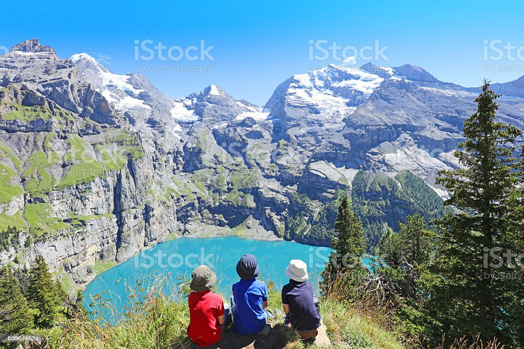 Children Hiking in Swiss Mountains Admiring Scenic Landscape at Oeschinensee stock photo