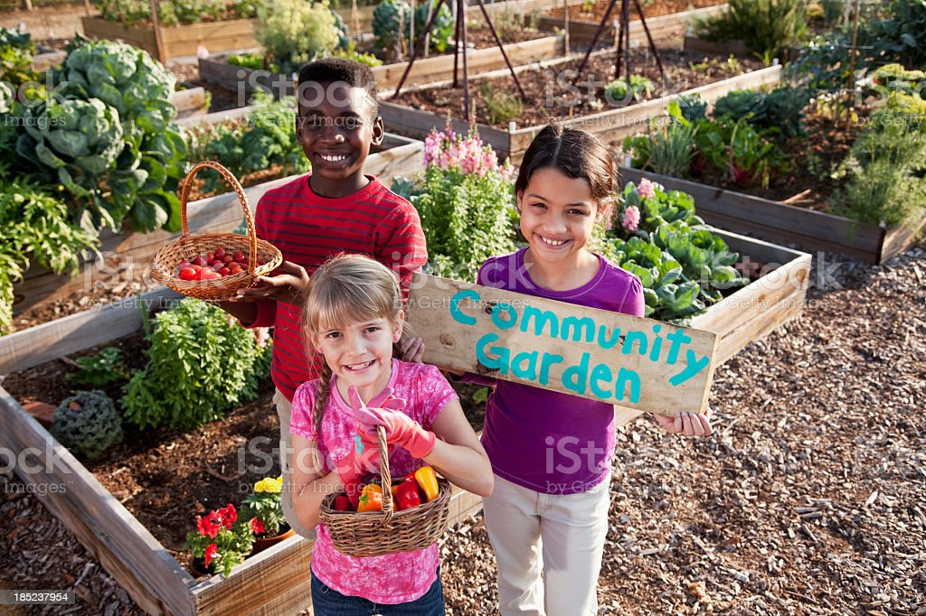 Children holding community garden sign stock photo