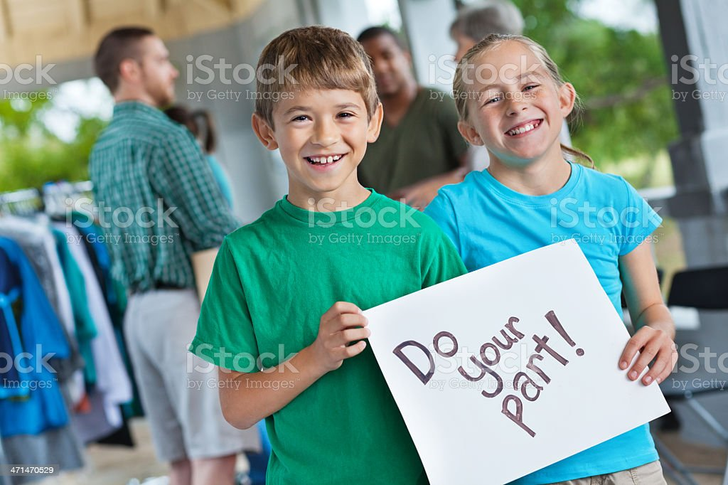Children holding 'do your part' sign at donation event royalty-free stock photo