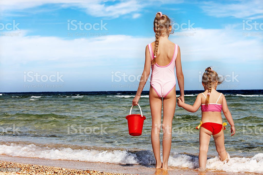 Children holding hands walking on the beach. royalty-free stock photo