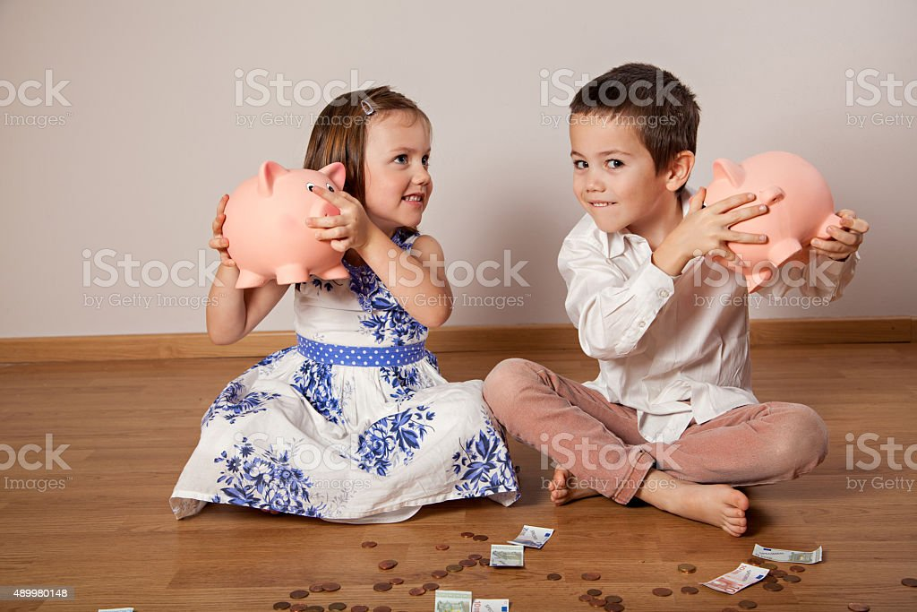 Children holding their piggy bank stock photo