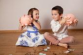 Children holding their piggy bank