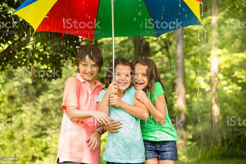 Children huddle under umbrella outdoors in rain. stock photo