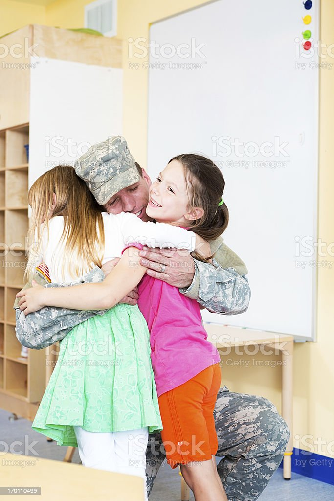 Children hugging a soldier stock photo