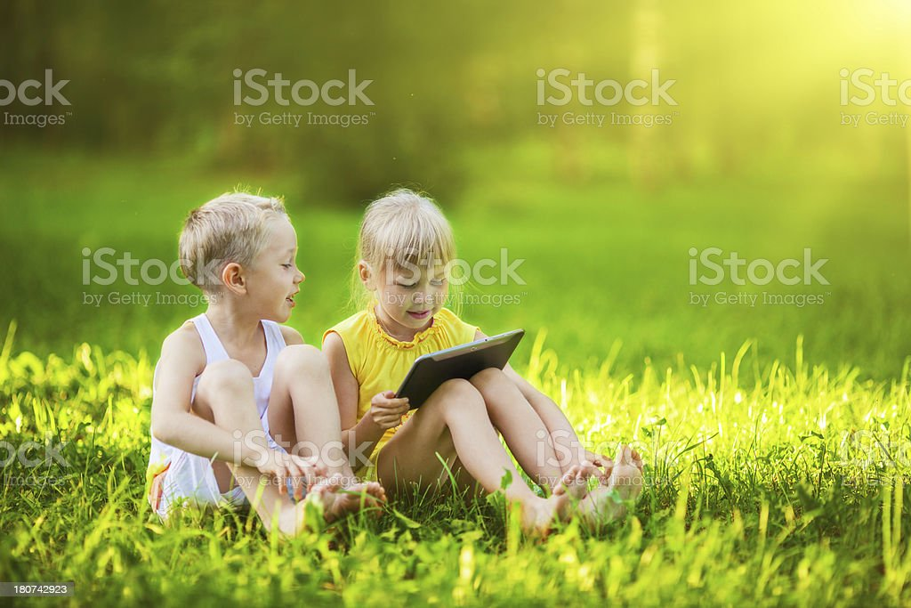 Children in a park using tablet royalty-free stock photo