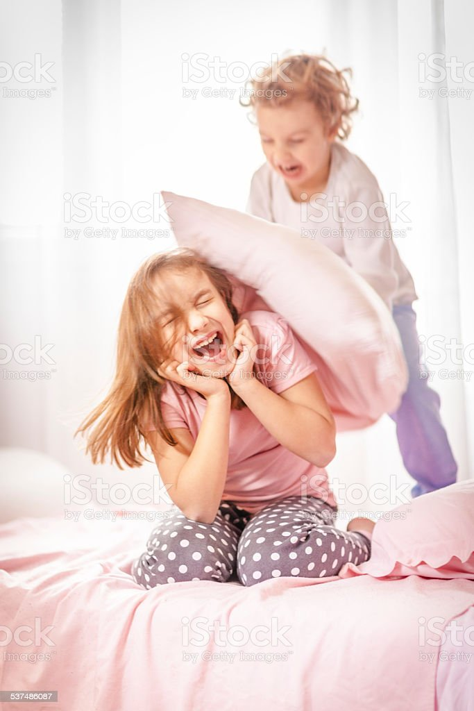 Children in a pillow fight stock photo