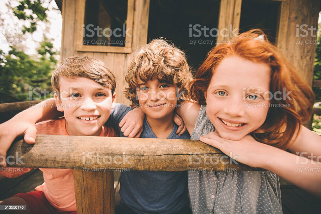 Children in a treehouse smiling together as friends stock photo