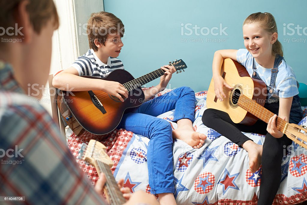Children In Bedroom Playing Guitars Together stock photo