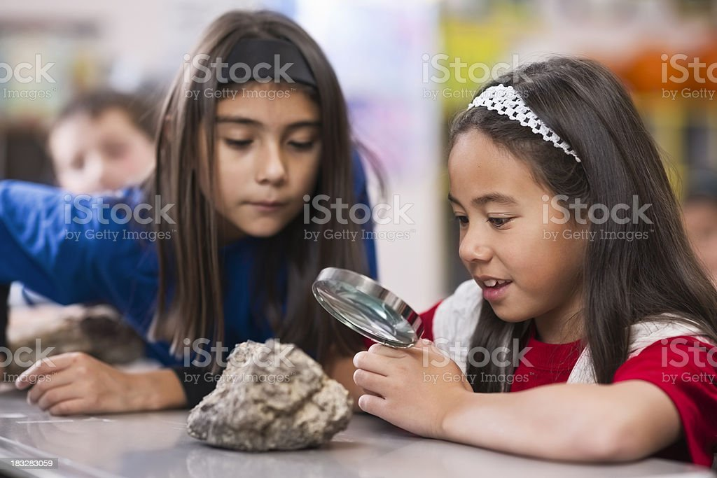 Children in Classroom With Magnifying Glass stock photo