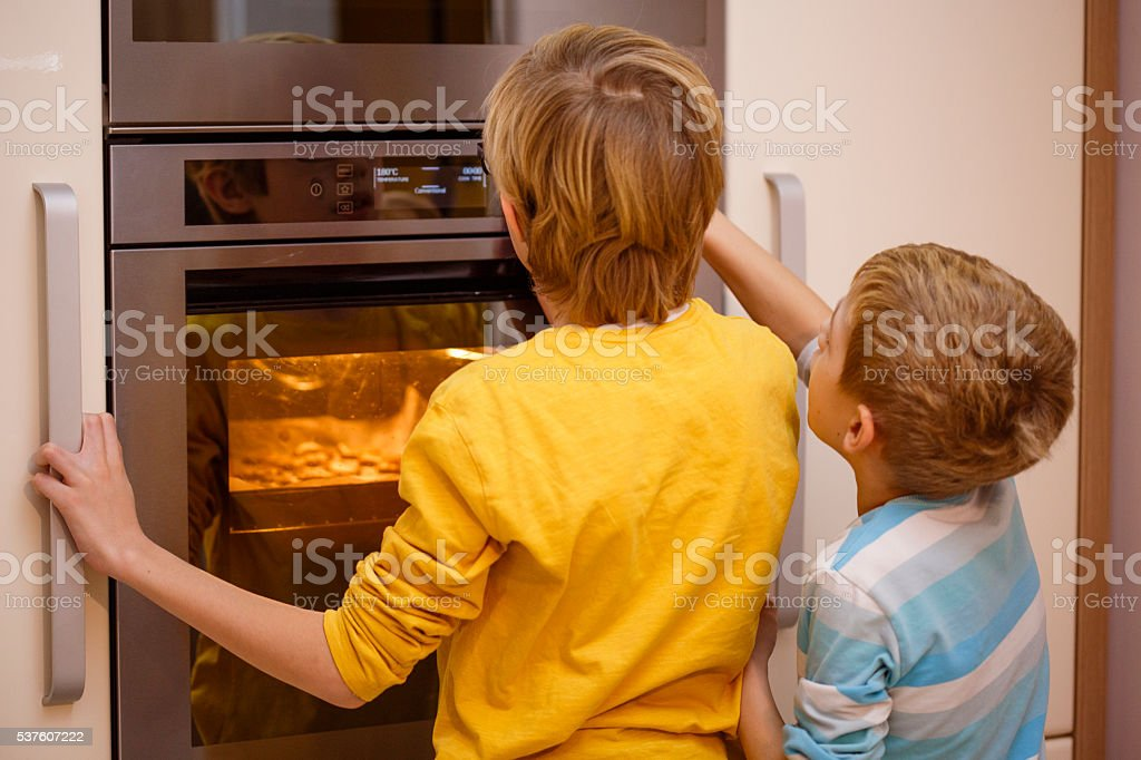 Children in front of oven stock photo