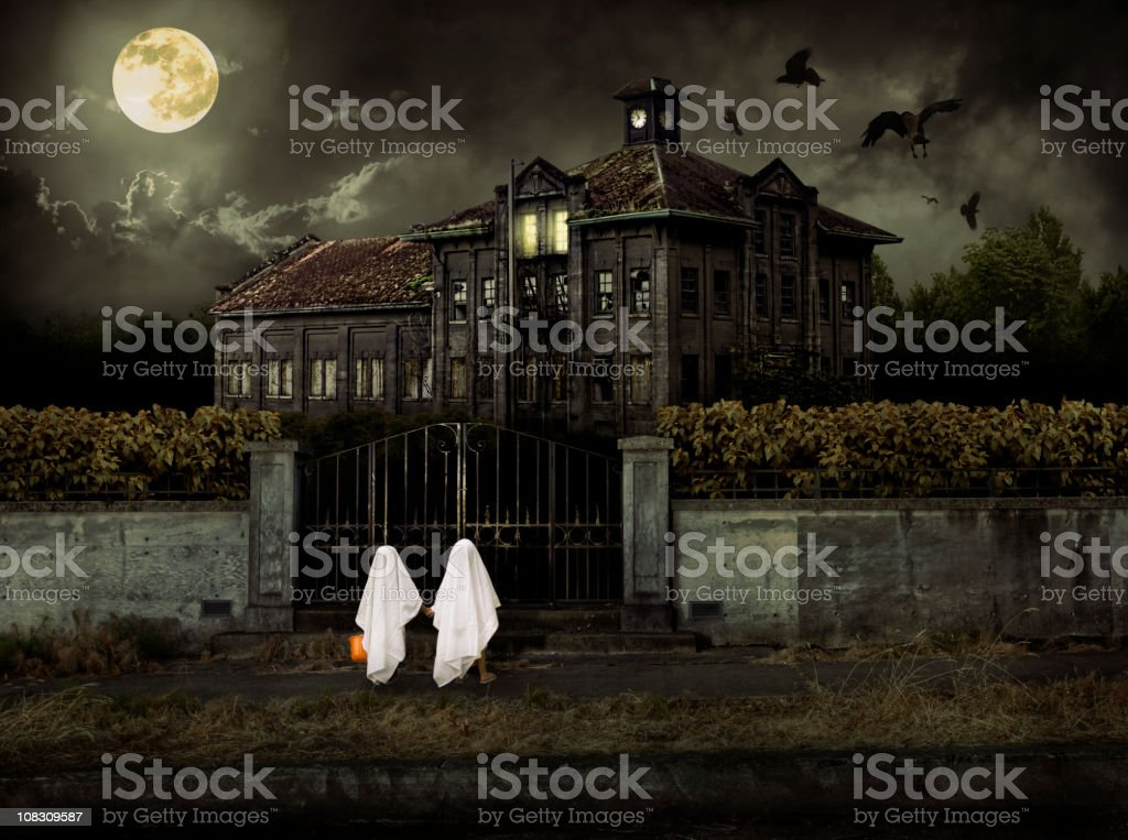 Children in Ghost Costumes Trick or Treat at Haunted House stock photo
