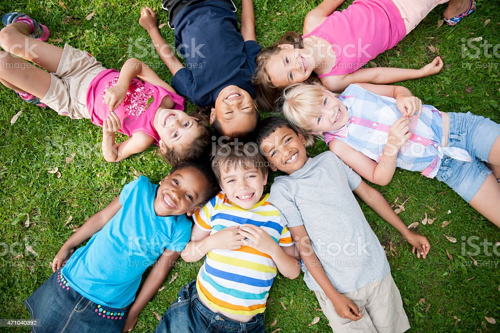 Children in Grass with Heads in Circle stock photo