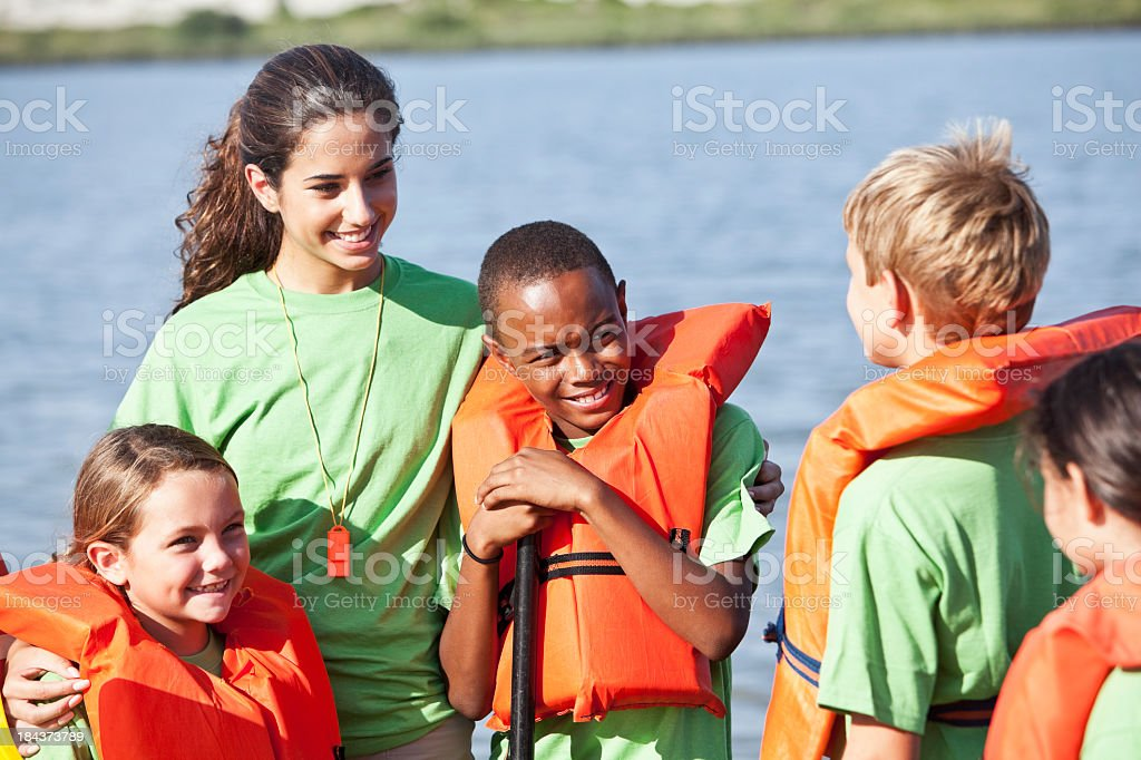 Children in life jackets with young woman at camp stock photo