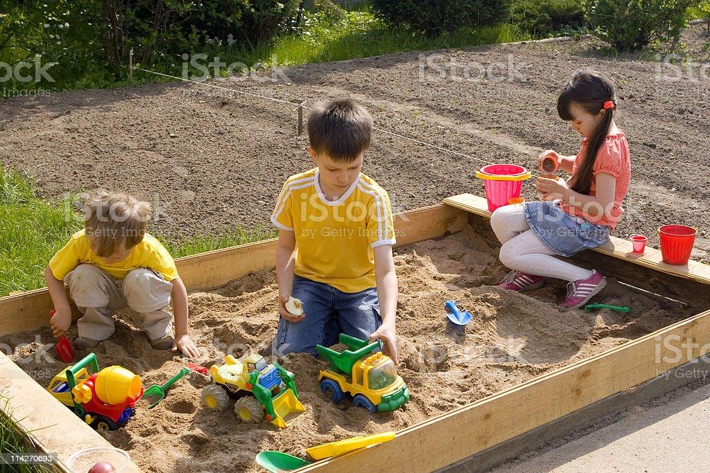 Children in sand-box stock photo