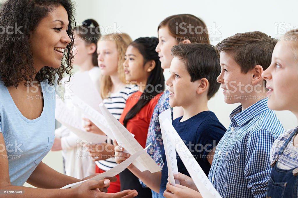 Children In School Choir Being Encouraged By Teacher stock photo