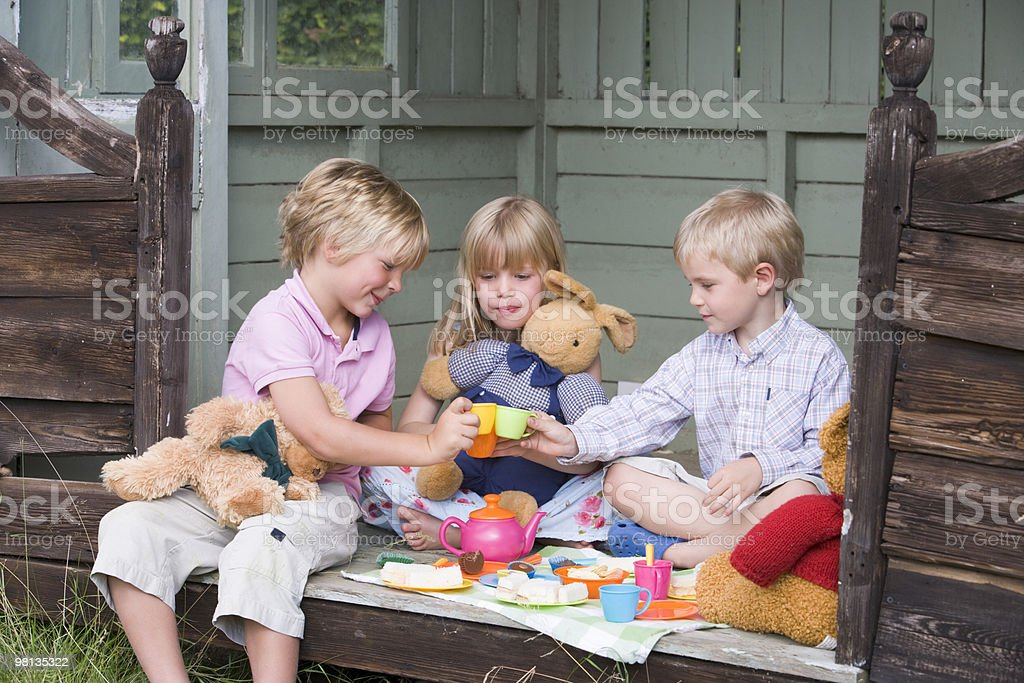 Children in shed playing tea stock photo