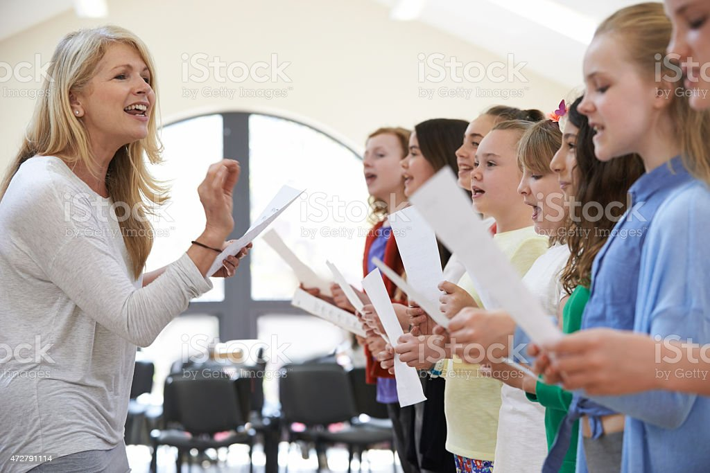 Children In Singing Group Being Encouraged By Teacher stock photo