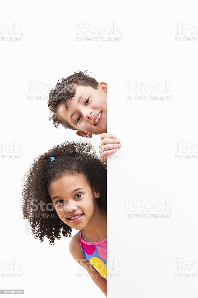 Children In Swimsuits Looking Around White Wall At Studio stock photo
