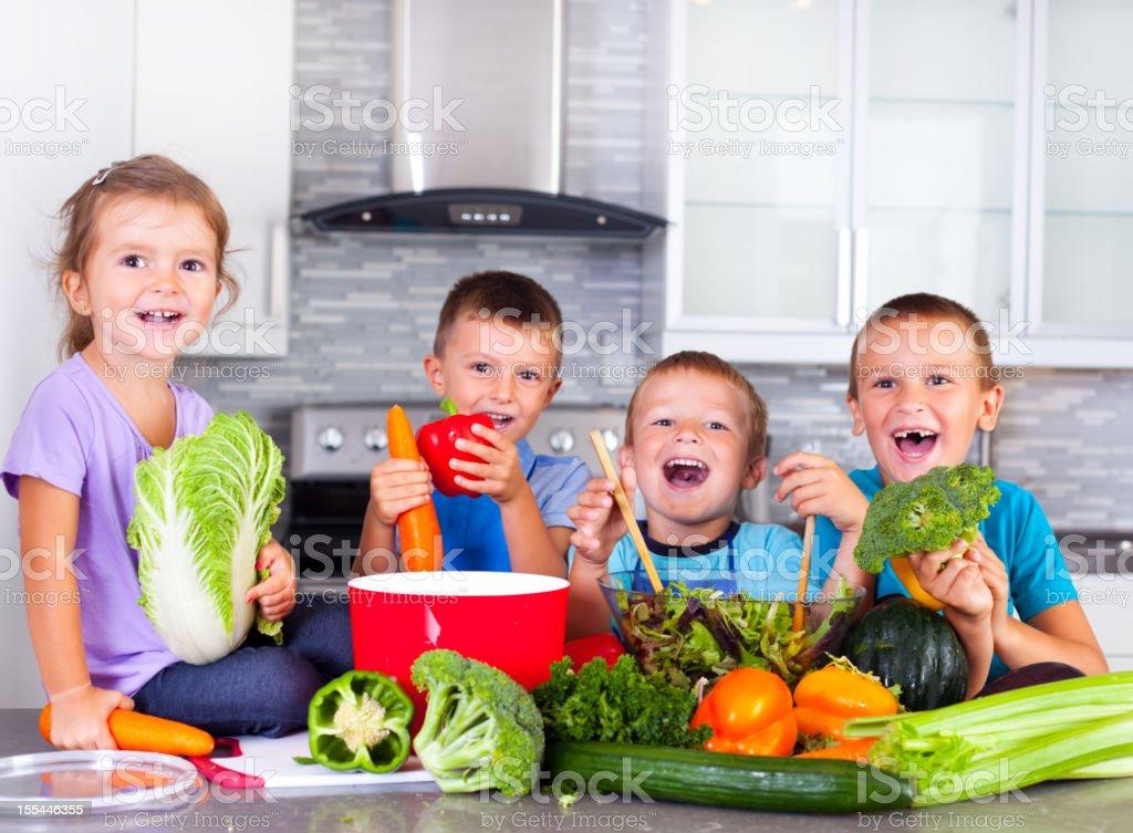 Children in the kitchen making dinner stock photo
