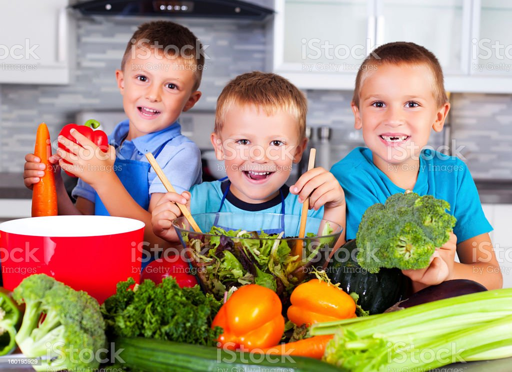 Children in the kitchen with healthy greens stock photo