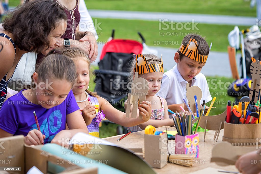 children in tiger costumes draw and create crafts stock photo