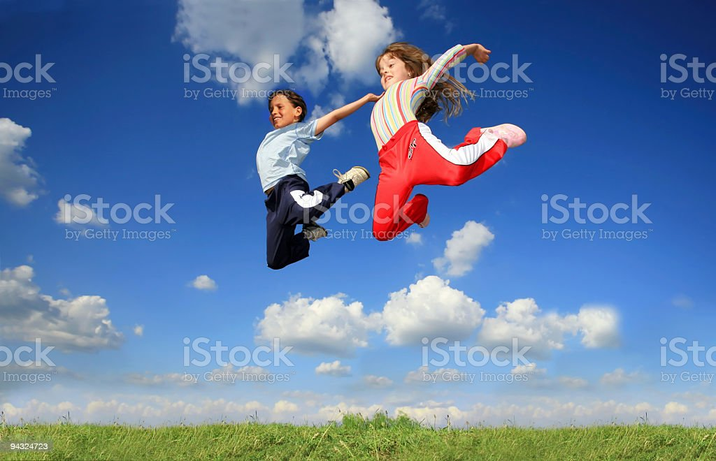 children jumping on meadow stock photo