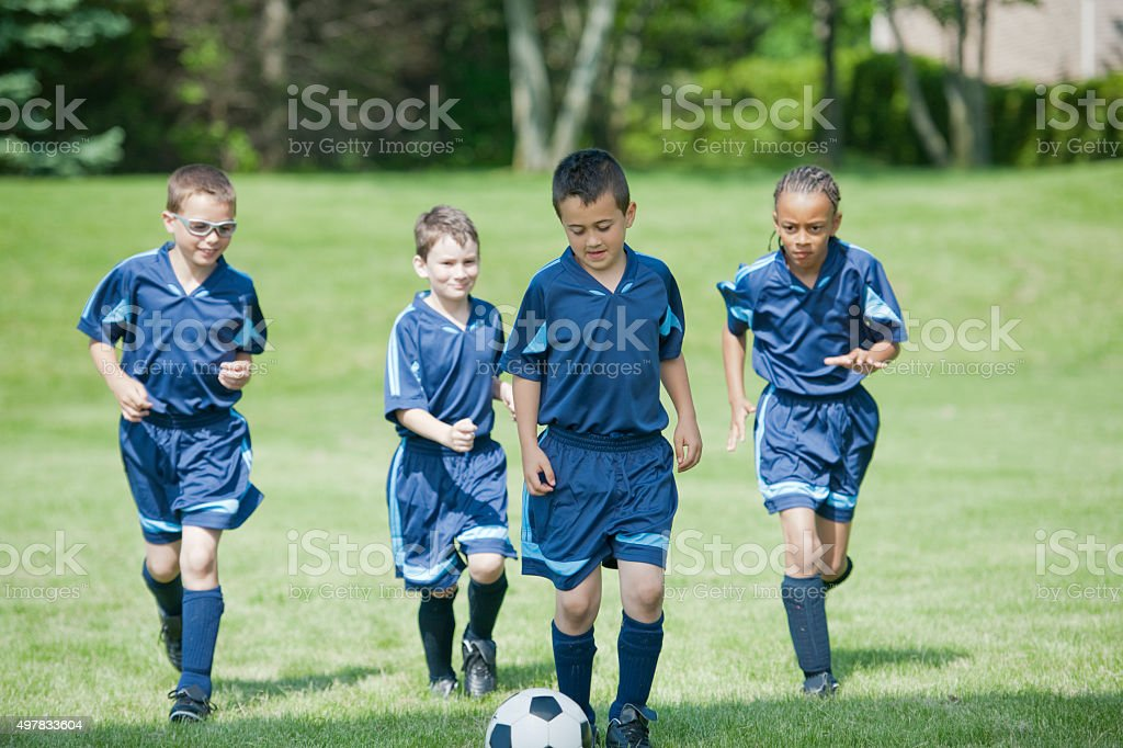 Children Kicking a Soccer Ball up the Field stock photo