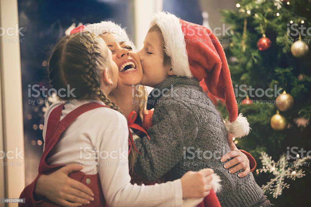 Children kissing mother on Christmas stock photo