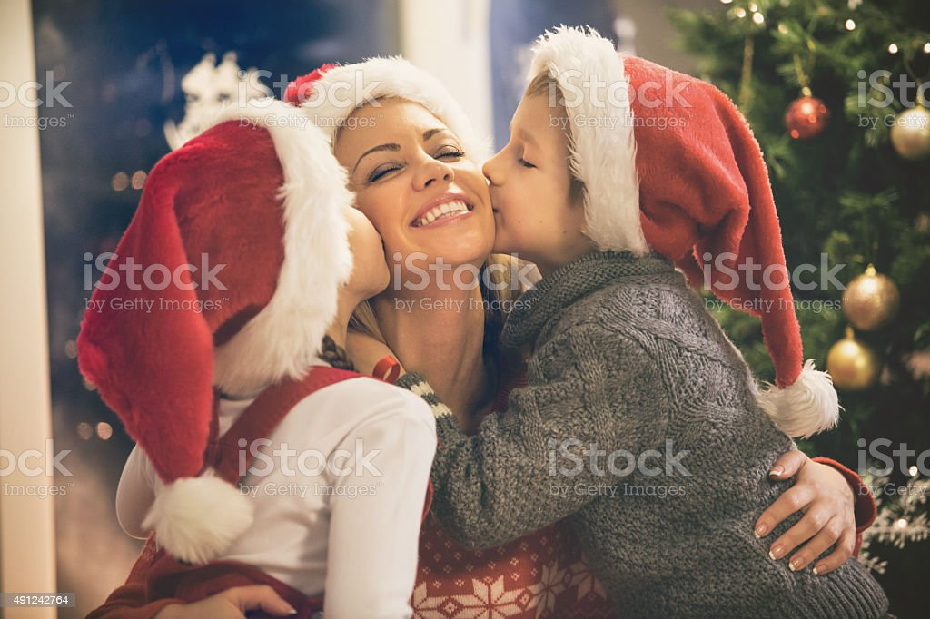 Children kissing their mother on Christmas stock photo