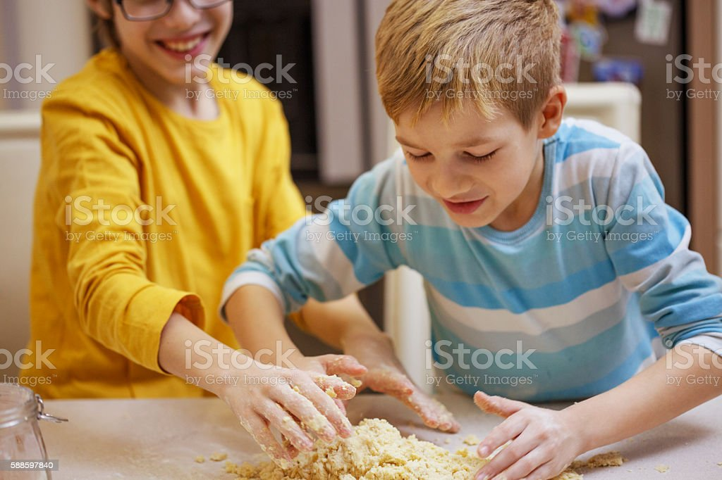 Children kneading dough together. stock photo