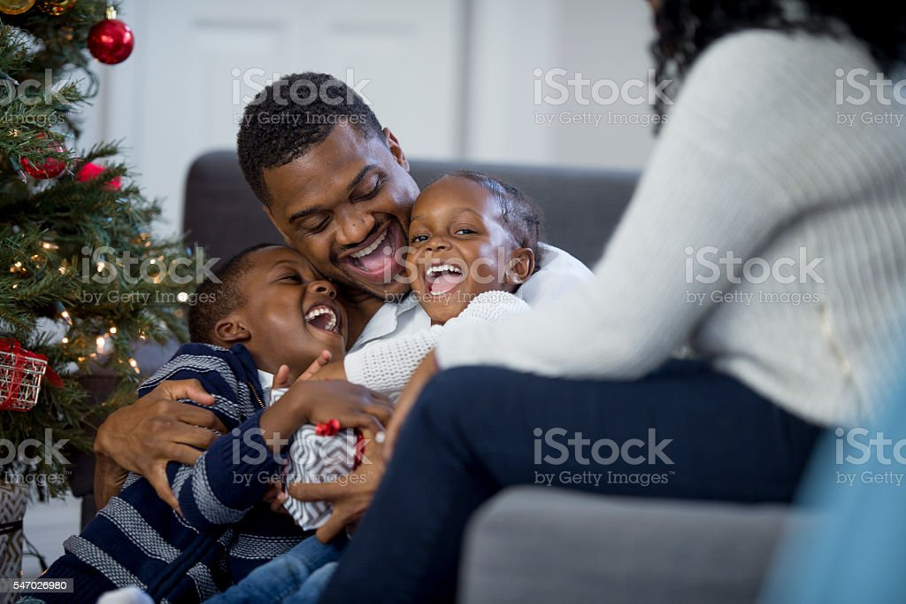 Children Laughing on Christmas Morning with Their Dad stock photo