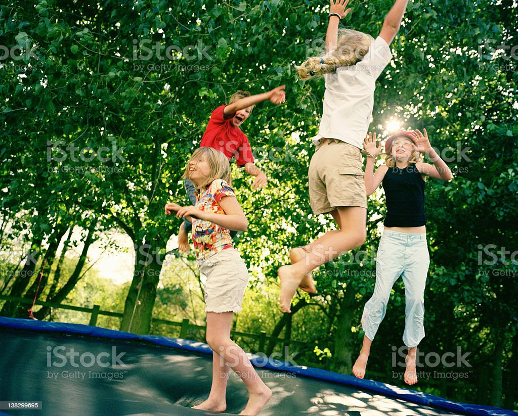 4 children leaping on trampoline stock photo