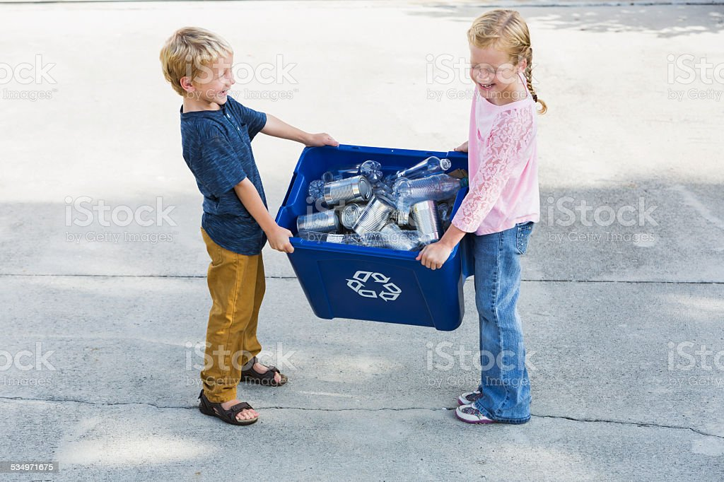 Children lifting recycling bin full of cans and bottles stock photo