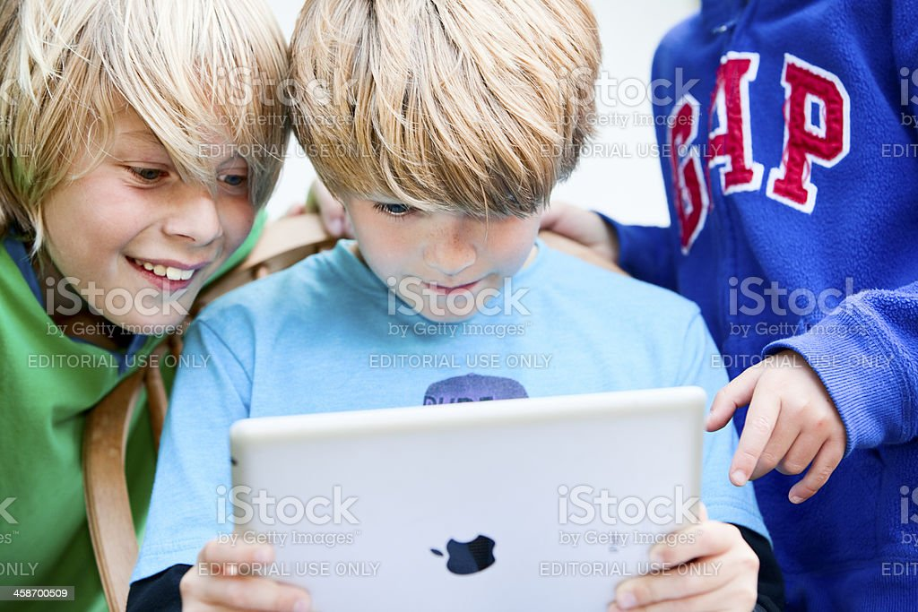 children looking at the screen of an iPad2 together stock photo