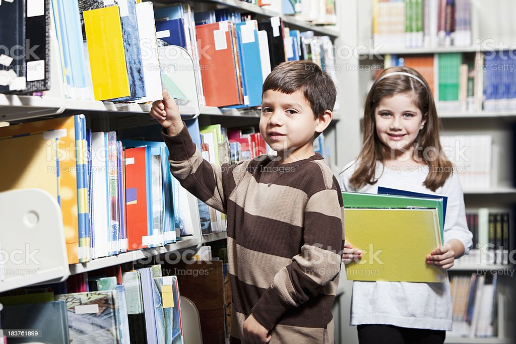 Children looking for books in library stock photo