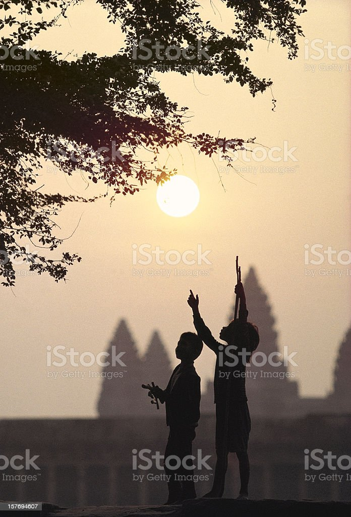 Children looking for Tamarinds at Angkor Wat. stock photo
