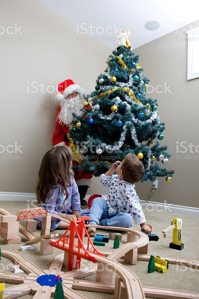 Children Looking Over Their Shoulders Seeing Santa Behind Tree royalty-free stock photo