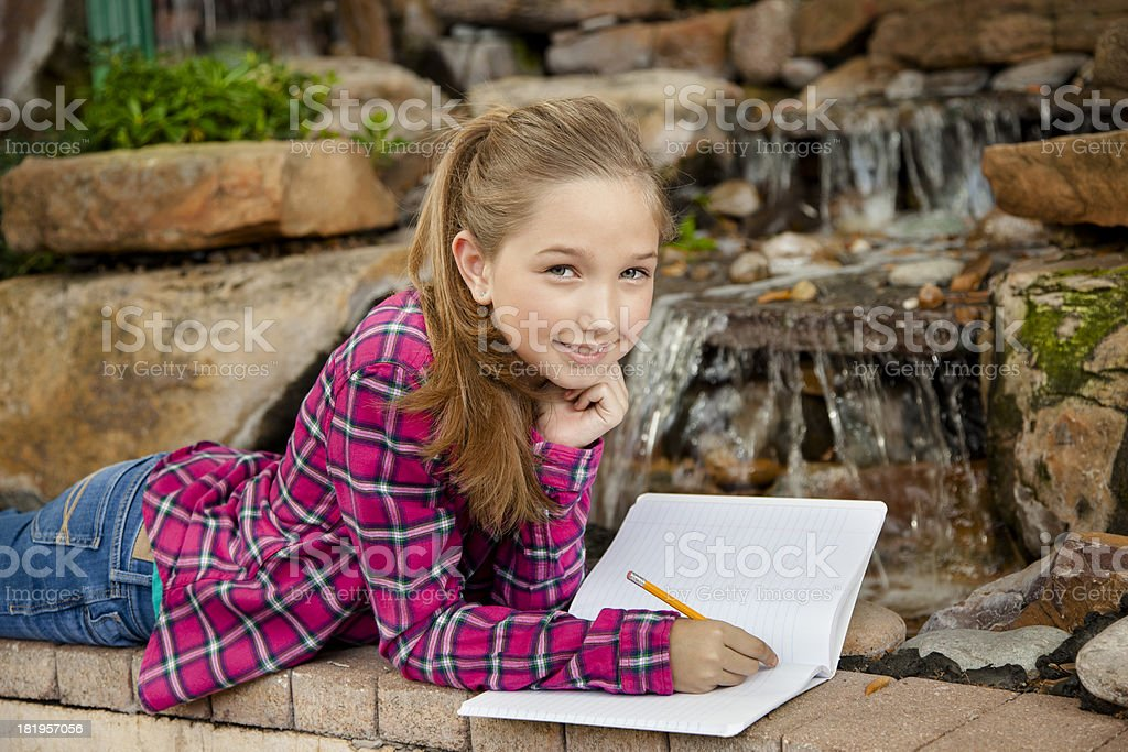 Children:  Lovely elementary girl writing in notebook by waterfall. royalty-free stock photo