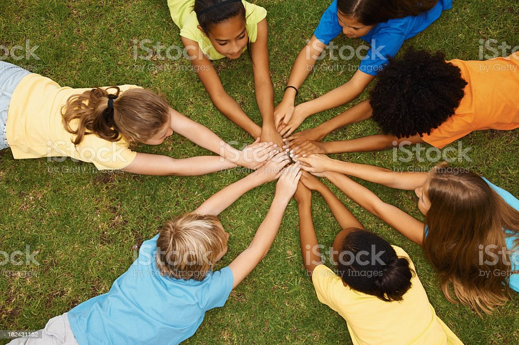 Children lying in a circle with their hands together royalty-free stock photo