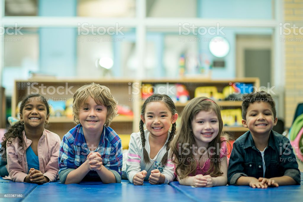 Children Lying in a Row Together stock photo