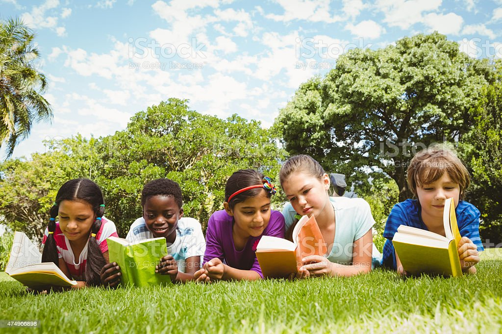 Children lying on grass and reading books stock photo